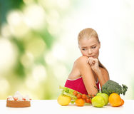 Doubting woman with fruits and pie Royalty Free Stock Photos