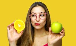 Doubting woman holding half orange and green apple and looking away. Close up portrait stock photos