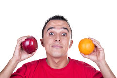 Doubting young Latino. Young man torn between an apple and an orange Stock Image