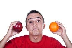 Doubting young Latino. Young man torn between an apple and an orange Stock Photos