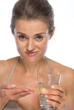 Doubting young woman with pill and glass of water Royalty Free Stock Photos