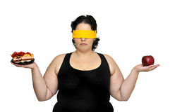 Doubts. Large girl blindfolded holding a cake and an apple isolated in white Royalty Free Stock Photography