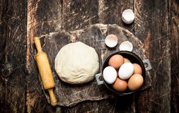 Dough background. The dough with a rolling pin and fresh eggs on old wooden Board. On wooden background Royalty Free Stock Photo