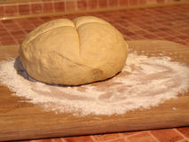 Dough. Ball of dough on wooden board ready to be baked royalty free stock images