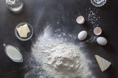 Dough on black table with flour and ingredients Royalty Free Stock Image