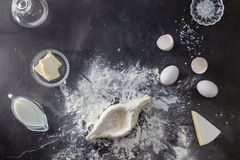 Dough on black table with flour and ingridients Royalty Free Stock Photos