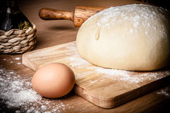 Dough on a board with flour. olive oil, eggs, rolling pin Stock Photography