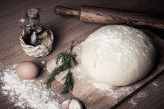 Dough on a board with flour. olive oil, eggs, rolling pin, garli Stock Photos