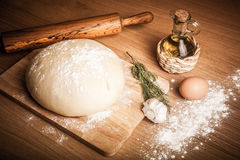 Dough on a board with flour. olive oil, eggs, rolling pin, garli Royalty Free Stock Photography