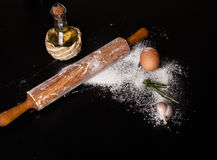 Dough on a board with flour. olive oil, eggs, rolling pin, garli Stock Photography