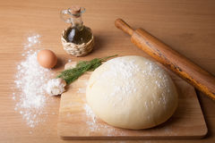 Dough on a board with flour. olive oil, eggs, rolling pin, garli Royalty Free Stock Photos