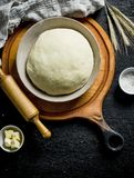 Dough in a bowl on a cutting Board. On black rustic background stock photo