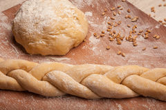 Dough braid on flour. On wooden desk Royalty Free Stock Image