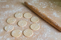 Dough circles and rolling pin. The dough rolled with circles and rolling pin for made ravioli on a wooden table Stock Image