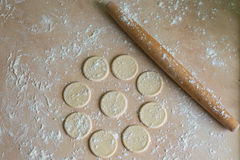 Dough circles and rolling pin. The dough rolled with circles and rolling pin for made ravioli on a wooden table Stock Photography