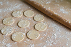 Dough circles and rolling pin. The dough rolled with circles and rolling pin for made ravioli on a wooden table Stock Images