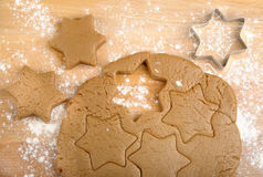Dough and cookie cutter. On a wooden background Stock Images