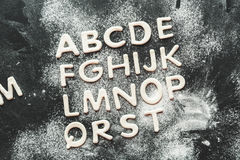 Dough for cookies in forms of letters with flour, cookie dough stock photos