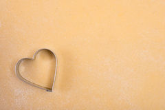 Dough with cutter in heart shape Royalty Free Stock Images
