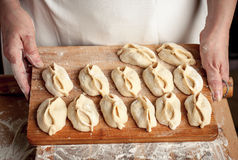 Dough_7. Dumplings on the wooden board in woman hands Stock Photography