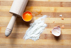 Dough - egg, flour, rolling pin on the wood board Stock Photos