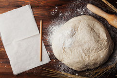 Dough with flour, baking paper, rolling pin, wheat ears on rustic table top view. Homemade pastry for bread or pizza. Stock Photo