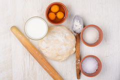 Dough, flour, eggs, milk, salt, sugar, baking ingredients Royalty Free Stock Photos
