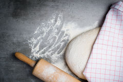 Dough, flour and rolling pin on a stone table Royalty Free Stock Images