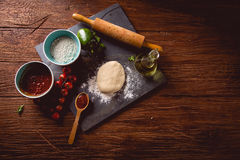 Dough with flour on wooden table, preparing homemade pizza Royalty Free Stock Image