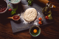 Dough with flour on wooden table, preparing homemade pizza Stock Photos