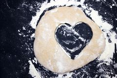 A dough heart on the table. An overhead photo of some flour, wheat dough and cookie cutter like a heart shape. A dough heart on the table. An overhead photo of stock image