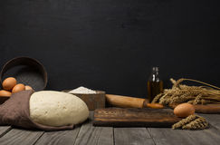 Dough with ingredients for cooking dough on wooden kitchen table. With blank space for your object Stock Images