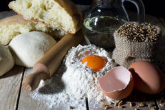 Dough, Loaf of Bread and Ingredients for Making Bread on Wooden Table Royalty Free Stock Image