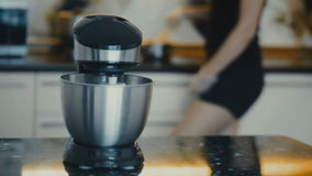 Dough mixing machine on desk in kitchen. Ingredients mixing steel bowl Woman stands near stove and cooks in pan Female stock video