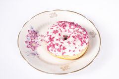 Dough-nut on plate. Donut on old hand painted china plate with roses isolated on white background Stock Images