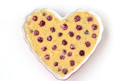 Dough for oatmeal cake with cherries in ceramic form in the shape of a heart on a white background. Top view stock images