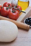 Dough and other ingredients for pizza. Stock Photo