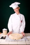 Dough on Pie Pan. Assertive uniformed smiling Pastry Chef displaying rolled pie dough over the pie pan Stock Photo