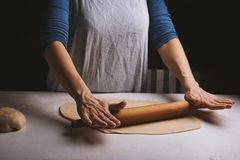 Dough and pin and female hands. Royalty Free Stock Image