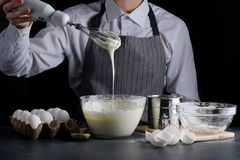 Dough pouring from the whisk. man manking pie. recipe concept on dark background royalty free stock images