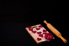Dough and raw red heart-shaped cookies on wooden board with flour, wooden rolling pin. Black table Stock Photos