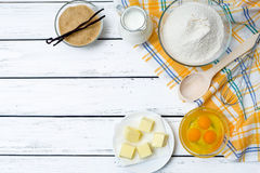 Dough recipe ingredients. Baking cake in rural kitchen - dough recipe ingredients (eggs, flour, milk, butter, sugar) on white wooden table from above Royalty Free Stock Images