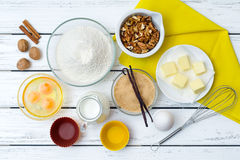 Dough recipe ingredients. Baking cake in rural kitchen - dough recipe ingredients (eggs, flour, milk, butter, sugar) with yellow napkin on white wooden table Stock Photo