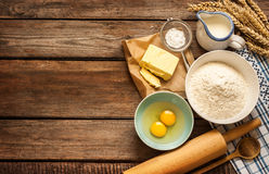 Dough recipe ingredients on vintage rural wood kitchen table. Baking cake in rural kitchen - dough recipe ingredients (eggs, flour, milk, butter, sugar) and Stock Image