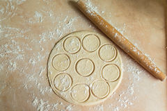 Dough rolled with circles, rolling pin. The dough rolled with circles and rolling pin for made ravioli on a wooden table stock photography