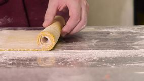 The dough is rolled into a straw. A cook in an apron rolls the dough into a straw on a metal table stock footage
