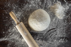 Dough and rolling pin with flour sprinkled lie on the kitchen ta. Ble Royalty Free Stock Image