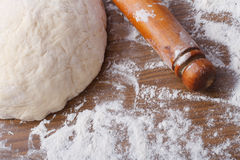 Dough with rolling pin on floured table Royalty Free Stock Image