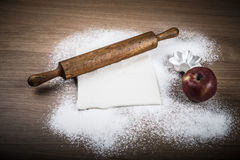 Dough, rolling pin, forms for baking, apple and flour sprinkled Royalty Free Stock Photo