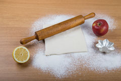 Dough, rolling pin, forms for baking, apple, half of lemon and f Royalty Free Stock Photos